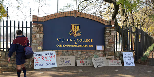 A student reads placards left at the entrance of the St. John's College in Johannesburg, South Africa, July 28, 2017.