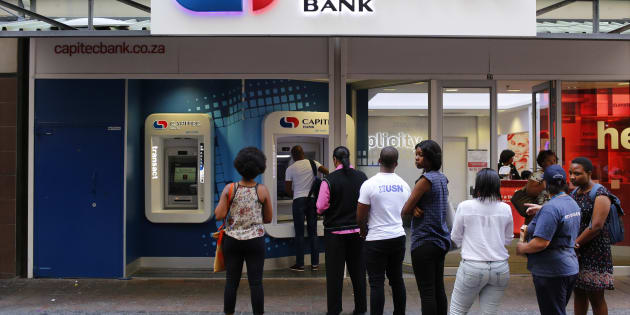 Customers queue to draw money from an ATM outside a branch of South Africa's Capitec Bank in Cape Town in this picture taken March 15, 2016. REUTERS/Mike Hutchings