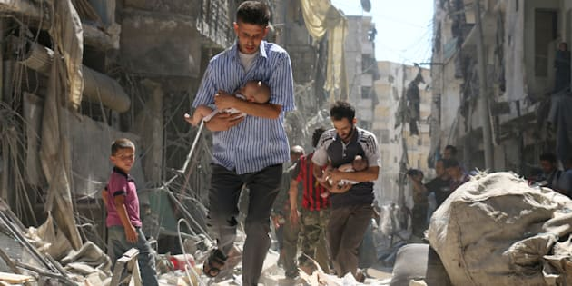 Syrian men carrying babies make their way through the rubble of destroyed buildings.
