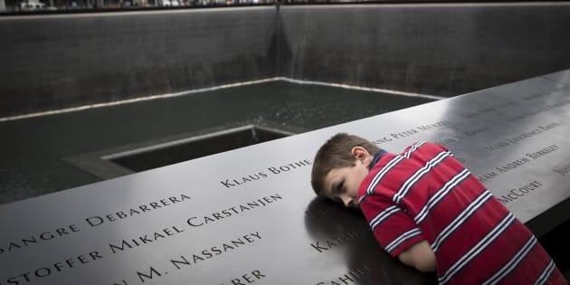 Un niño se inclina sobre el memorial de las víctimas del 11-S en Nueva York, en el aniversario del atentado en 2015.