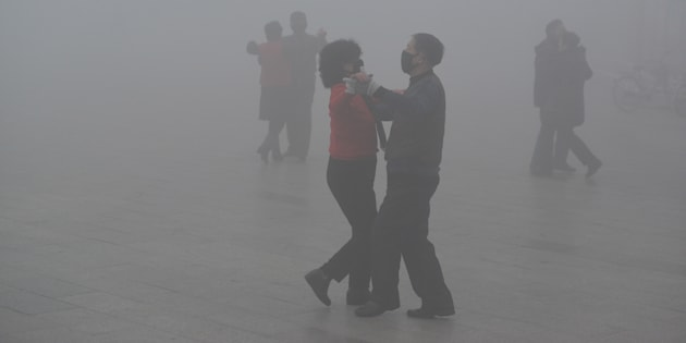 Des danseurs portent un masque dans un smog épais à Fuyang, en Chine.