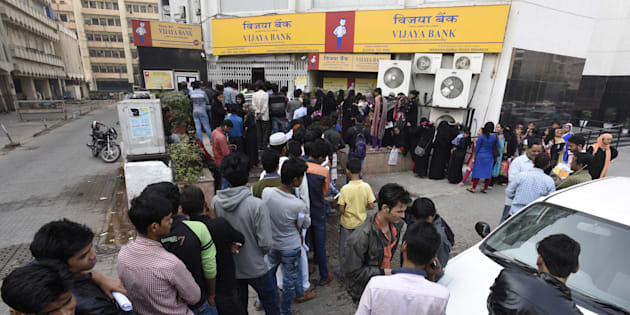 NEW DELHI, INDIA - NOVEMBER 24: People stand in a queue outside banks to deposit and exchange old denomination Indian rupee 500 and 1000 currency notes, at Barakhamba Road, on November 24, 2016 in New Delhi, India.