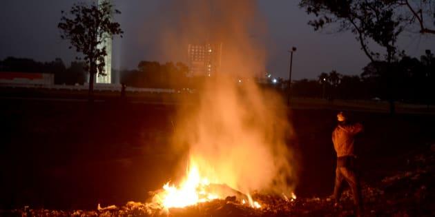 Un homme se réchauffe près d'un feu dans un parc de Dacca.