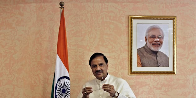 India's Culture Minister Mahesh Sharma, poses next to an Indian national flag and a portrait of India's Prime Minister Narendra Modi before an interview.