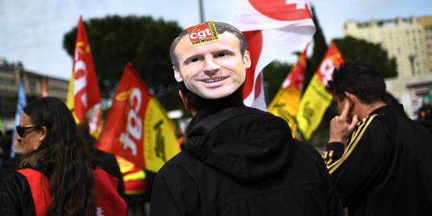 Un manifestant portant un masque à l'effigie du président Emmanuel Macron.