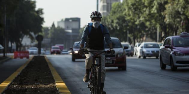 Un hombre monta una bicicleta con una máscara en la Ciudad de México.
