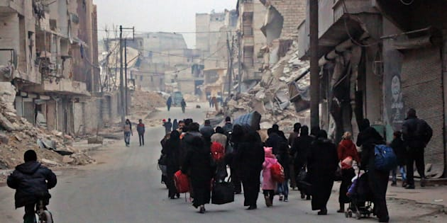 Syrian civilians flee the Sukkari neighbourhood towards safer rebel-held areas in southeastern Aleppo, on December 12, 2016, during an operation by Syrian government forces to retake the embattled city.  The crucial battle for Aleppo entered its 'final phase' after Syrian rebels retreated into a small pocket of their former bastion in the face of new army advances. The retreat leaves opposition fighters confined to just a handful of neighbourhoods in southeast Aleppo, the largest of them Sukkari and Mashhad.     / AFP / STRINGER        (Photo credit should read STRINGER/AFP/Getty Images)