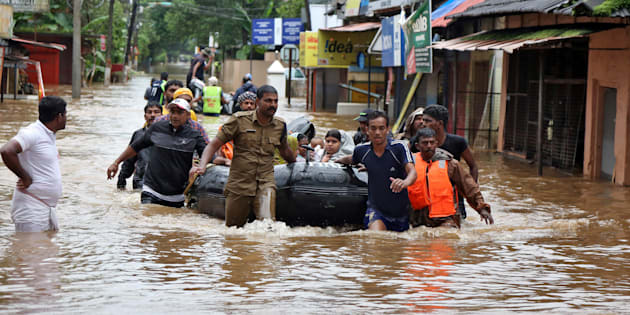 Rescuers evacuate people from a flooded area to a safer place in Aluva in Kerala on Saturday.