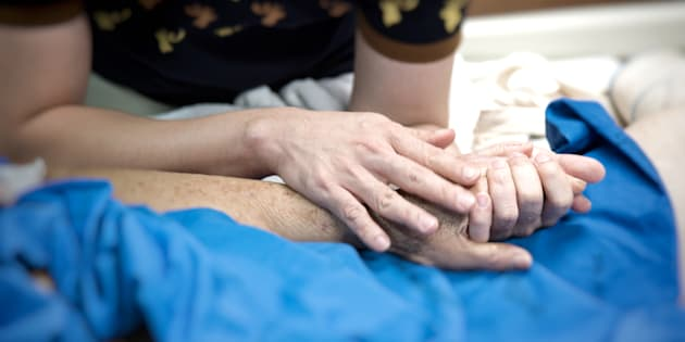 Patient in the hospital with saline intravenous and relatives patient hand holding a elderly patient hand