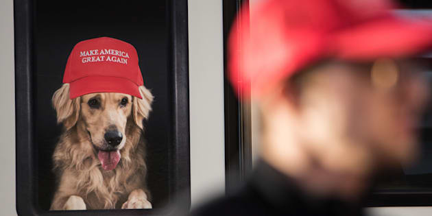 A man stands near a Donald Trump campaign vehicle with an image of a dog in a window before a campaign rally on Feb. 5, 2016, in South Carolina.