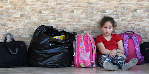A Palestinian refugee who fled the Ain al-Hilweh camp, Lebanon's largest Palestinian refugee camp, due to ongoing clashes between Palestinian security forces and Islamist fighters for the third consecutive day, is seen sitting next to her belongings at a mosque in the southern coastal city of Sidon on Aug. 19, 2017.