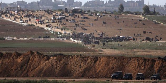 Des véhicules militaires israéliens aux abords de la frontière entre Gaza et Israël et des manifestants palestiniens.
