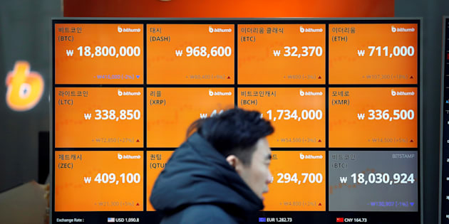 A man walks past an electric board showing exchange rates of various cryptocurrencies including Bitcoin (top L) at a cryptocurrencies exchange in Seoul, South Korea December 13, 2017.
