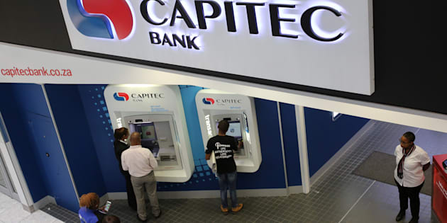 Customers queue to draw money from an ATM outside a branch of South Africa's Capitec Bank in Johannesburg.