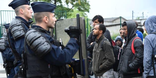 Des CRS face aux migrants attendant de pouvoir monter dans des bus, le 18 août à la porte de La Chapelle.