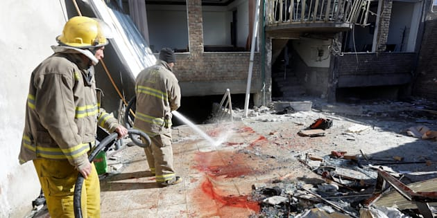 Afghan fire fighters spray water to remove the bloodstains at the site of a suicide attack in Kabul, Afghanistan Dec. 28, 2017.