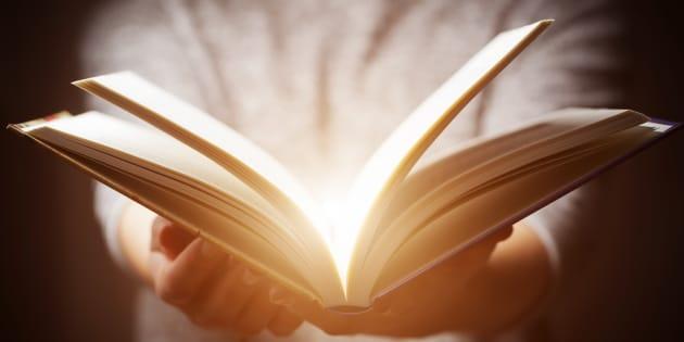 Luz saliendo de un libro sostenido por una mujer.