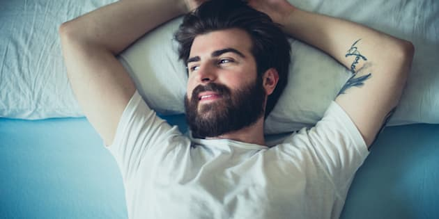 Portrait of handsome bearded man in the bed