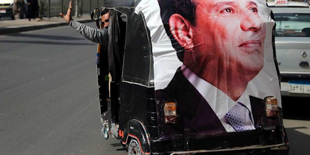 A man gestures as he rides a motorized vehicle showing a poster of Egyptian President Abdel Fattah al-Sisi during the second day of the presidential election in Cairo, Egypt, March 27, 2018. REUTERS/Ammar Awad