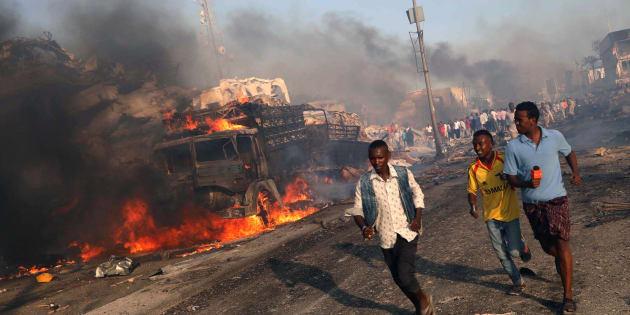 Un grupo de ciudadanos y de reporteros, evacuados de la zona del atentado, donde aún arde uno de los camiones, el sábado en Mogadiscio.