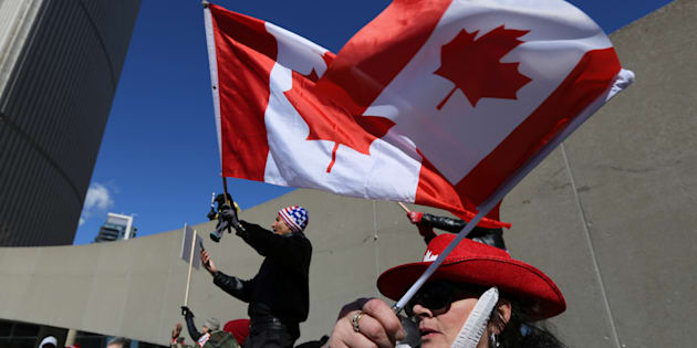 Opponents of the anti-Islamophobia federal government motion M-103 wave Canadian flags during a rally outside City Hall in Toronto, Ontario, Canada March 4, 2017.