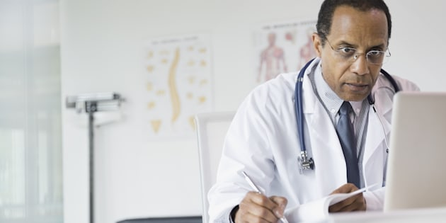 Male doctor taking notes in office.