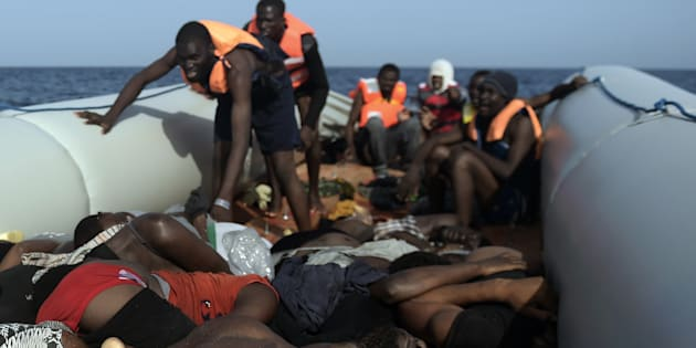 TOPSHOT - EDITORS NOTE: Graphic content / Migrants step over dead bodies while being rescued by members of Proactiva Open Arms NGO in the Mediterranean Sea, some 12 nautical miles north of Libya, on October 4, 2016. Twenty-eight Europe-bound migrants were found dead on a day of frantic rescues off Libya, including at least 22 in an overloaded wooden boat, an AFP photographer and the Italian coastguard said.  / AFP / ARIS MESSINIS        (Photo credit should read ARIS MESSINIS/AFP/Getty Images)