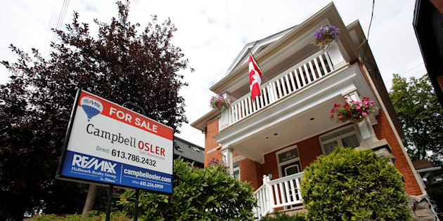 A real estate sign is seen in front of a house for sale in Ottawa, Aug. 15, 2017.