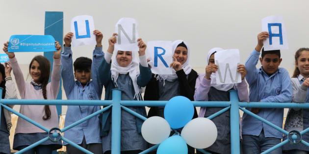 """Unos niños refugiados palestinos forman la palabra """"UNRWA"""" en una protesta contra los recortes de EEUU, en Sebline, Líbano."""