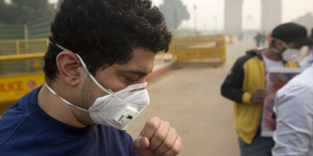 A man coughs even after wearing a mask a day after Diwali festival in New Delhi