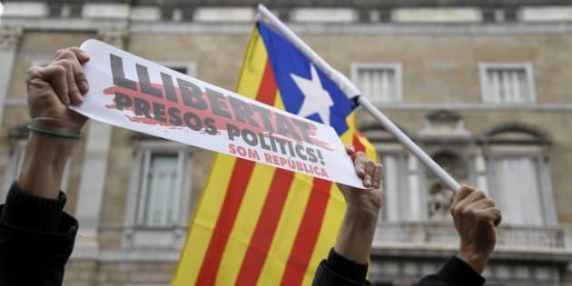 """Des manifestants brandissent le slogan """"Libérez les prisonniers politiques"""" et le drapeau catalan pro-indépendance lors d'une manifestation à Barcelone le 8 novembre 2017."""