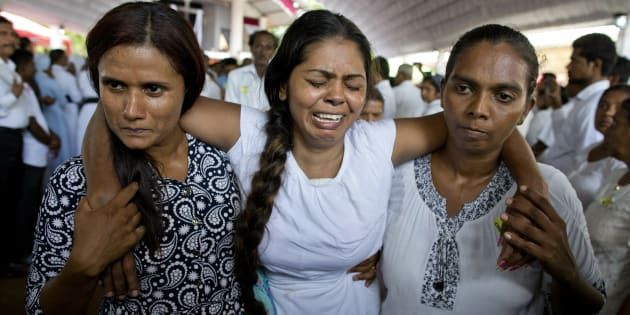 A grieving woman is supported during a funeral service at St. Sebastian Church in Negombo, Sri Lanka, for Easter Sunday bomb blast victims on April 23, 2019. More than 320 people were killed in the attacks.