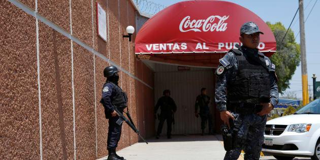 Policías protegen la entrada de la planta de distribución de Coca-Cola FEMSA luego de su cierre debido a problemas de seguridad y violencia en Ciudad Altamirano en el estado de Guerrero, México 3 de abril de 2018 .