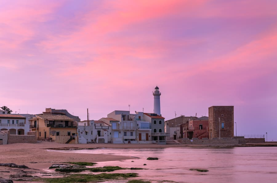 Sunrise at Punta Secca Beach with the lighthouse and the watchtower,Torre Scalambri in Santa Croce Camerina, Sicily, Italy