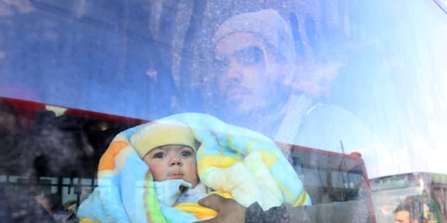 A man with a baby rides a bus to be evacuated from a rebel-held sector of eastern Aleppo, Syria December 18, 2016. Picture taken December 18, 2016. REUTERS/Abdalrhman Ismail