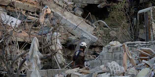 A rescue worker searches the debris of a collapsed hospital in Idlib Province on Feb. 15, 2016.