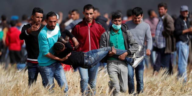 Un grupo de palestinos traslada a un joven alcanzado por la carga de los soldados del Israel, el pasado 13 de abril en la frontera de Gaza.