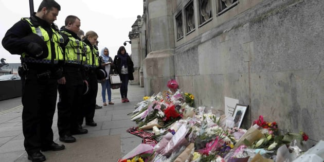 Police officers and civilians look at floral tributes near Westminster Bridge following a recent attack in Westminster, in London, Britain March 24, 2017.