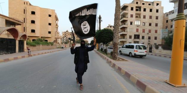 Un miembro del Estado Islámico enarbola su bandera en la ciudad siria de Raqqa, en junio de 2014.