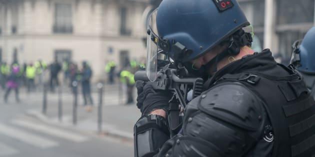 Un gendarme mobile tient un LBD40 face à des gilets jaunes, lors de l'Acte IV, le 8 décembre 2019.