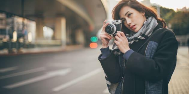 Reportera japonesa tomando una fotografía en la ciudad. El movimiento Me Too inspira a periodistas japonesas a crear una asociación en contra del acoso sexual.