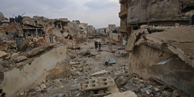 Des Syriens marchent à travers les ruines d'Alep dévastée, le 17 décembre 2016