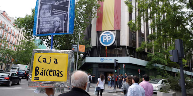 Un hombre sostiene un 'réplica' de la caja b de Bárcenas, ante la sede del PP en Madrid.