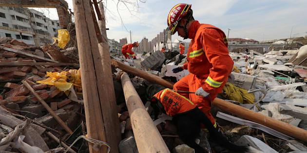 A rescue worker works with a rescue dog at the site of a blast in Ningbo, Zhejiang province, China.