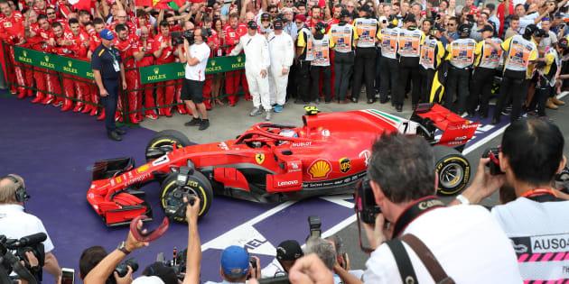 The team of Ferrari's German driver Sebastian Vettel waits to congratulate him after he won the Formula One Australian Grand Prix in Melbourne on March 25, 2018