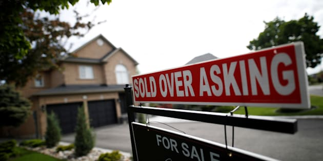 "A real estate sign that reads ""For Sale"" and ""Sold Above Asking"" stands in front of housing in a Toronto suburb on May 24, 2017."
