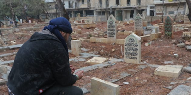 ALEPPO, SYRIA - DECEMBER 14:  A man prays over the graves of family members in al-Mashhad neighborhood in Aleppo, Syria on December 14, 2016.  (Photo by Ibrahim Ebu Leys/Anadolu Agency/Getty Images)