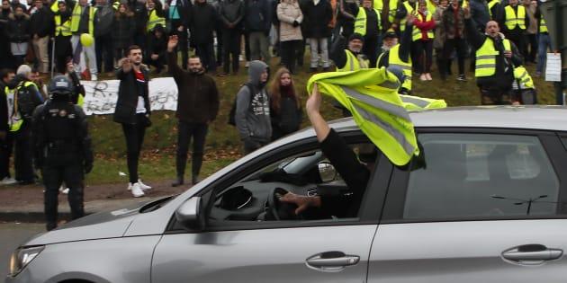 Un conducteur brandit un gilet jaune pour afficher son soutien au mouvement le 15 janvier 2019 à Grand Bourgtheroulde en Normandie.