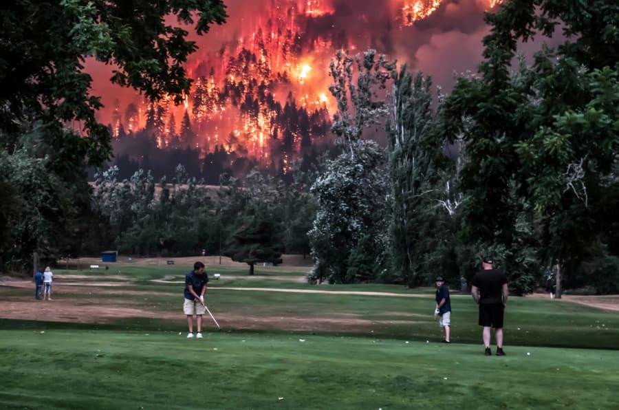 El bosque de Eagle Creek arde mientras varios golfistas juegan en el Campo de Golf Beacon de North Bonneville, en Washington, EEUU, el 4 de septiembre de 2017.