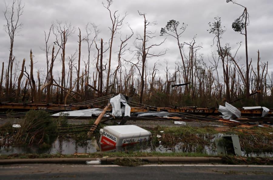 Árboles destrozados, carros de trenes descarrilados y sumergidos son vistos después de que Michael azotó Panama City, Florida.